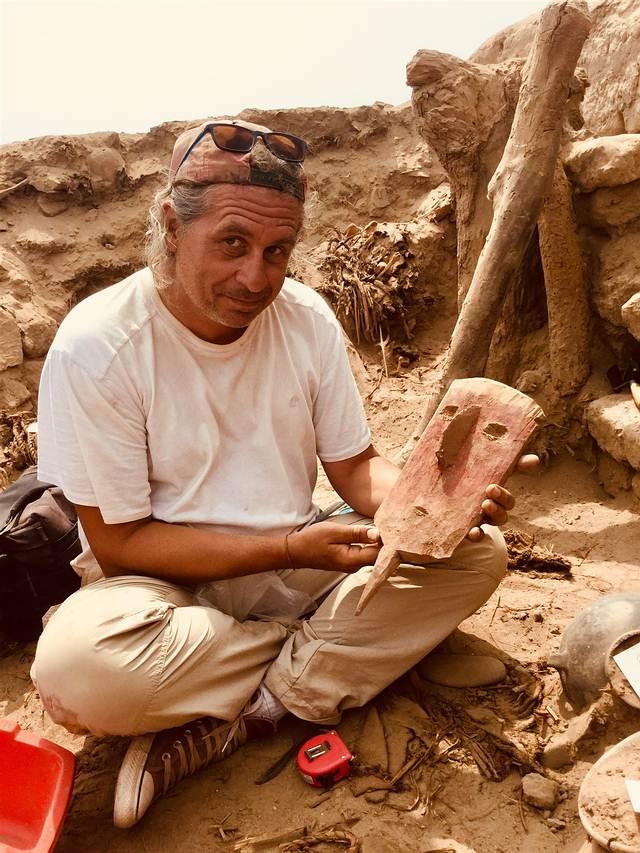 El arqueólogo Peter Eeckhout con una máscara de madera que estaba colocada sobre la cabeza de una momia que ya no se conserva porque fue saqueada.