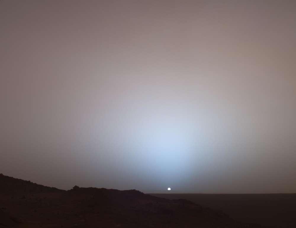 Amplia vista de una puesta de sol sobre el cráter Gusev tomada por el Spirit Rover de la NASA en 2005. Se ven la aureola azul y el cielo rosado