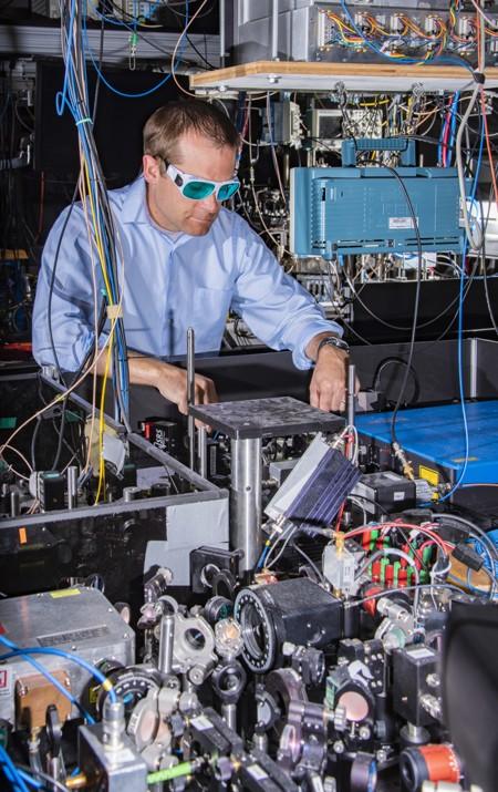 El físico Andrew Ludlow del NIST y sus colegas lograron nuevos registros de rendimiento del reloj atómico en una comparación de dos relojes de celosía óptica de iterbio. Los sistemas láser utilizados en ambos relojes son visibles en primer plano, y el aparato principal de uno de los relojes se encuentra detrás de Ludlow