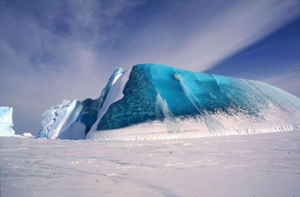 Un iceberg parcialmente volcado incrustado en el hielo marino. El hielo azul claro está hecho de hielo marino