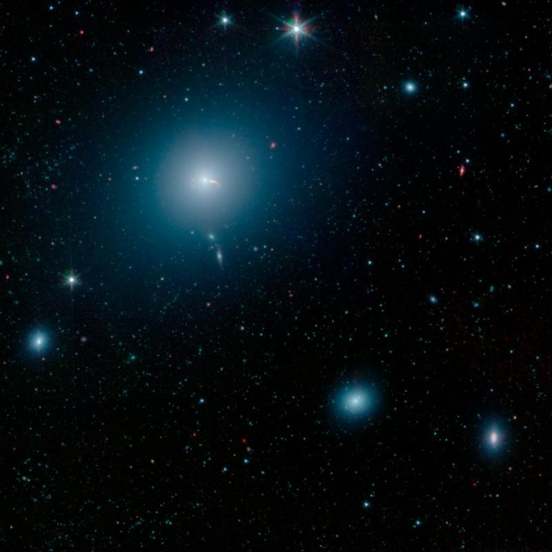 La galaxia M87 se ve como un nebuloso espacio azul en esta imagen del Telescopio Espacial Spitzer de la NASA. En el centro de la galaxia hay un agujero negro supermasivo que arroja dos chorros de material al espacio