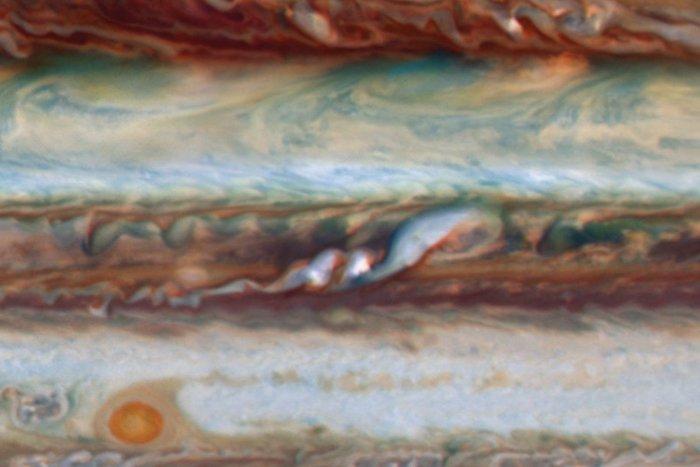 Dos penachos blancos brillantes (centro) en Júpiter, con una perturbación aguas abajo más grande a su derecha